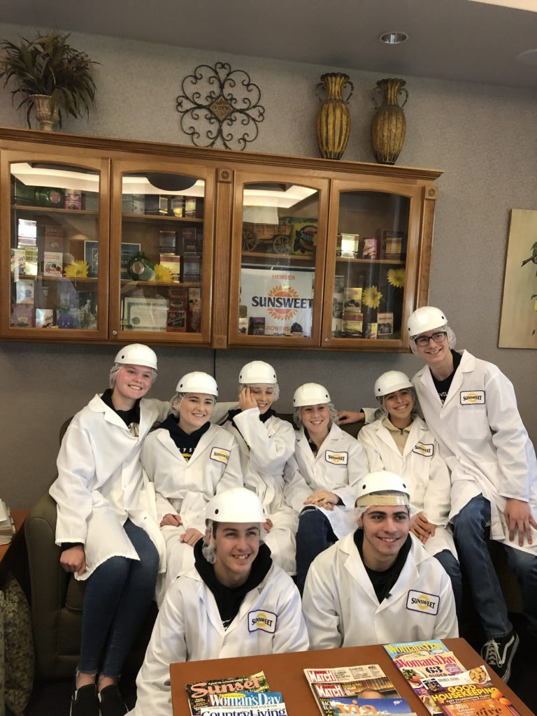 Students pose in front of a cabinet in lab coats and hard hats.