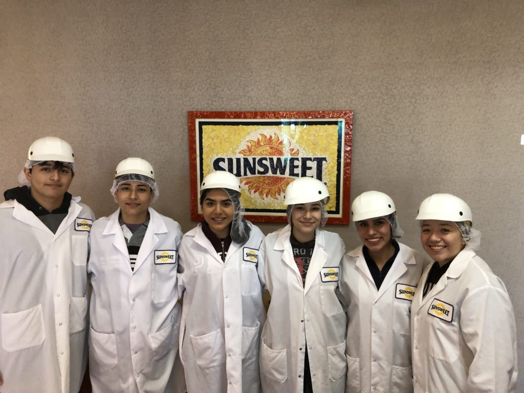 Students pose in front of a Sunsweet sign wearing lab coats and hard hats.