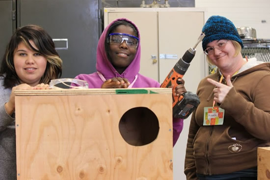 an image of 3 students working with power tools in a woodshop