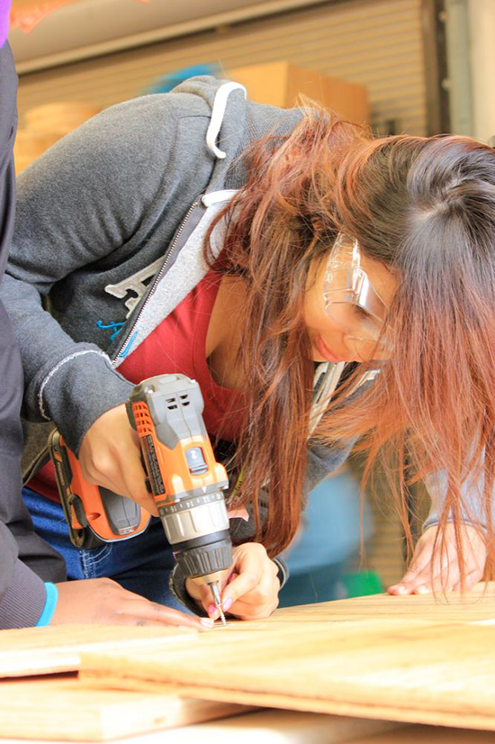 an image of a young girl using a power screwdriver to drill into some wood