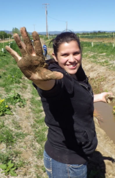 a SLEWS student holding out her hand covered in mud